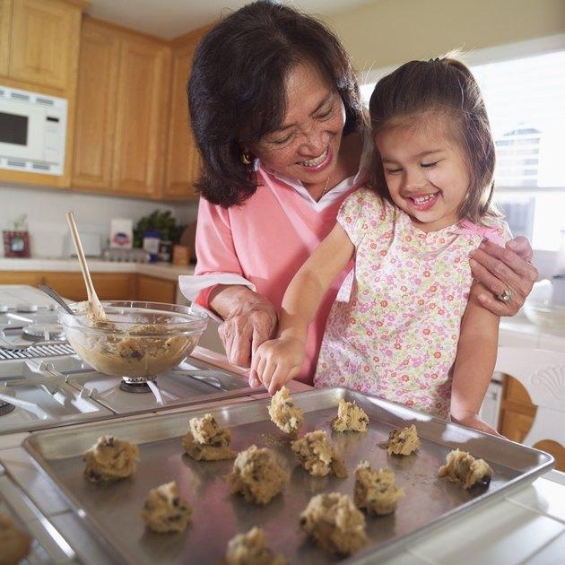 Grandmother helping granddaughter bake cookies