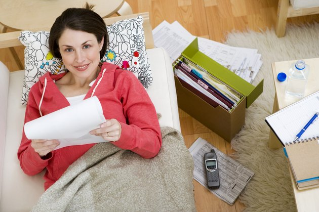 Woman on sofa with paperwork
