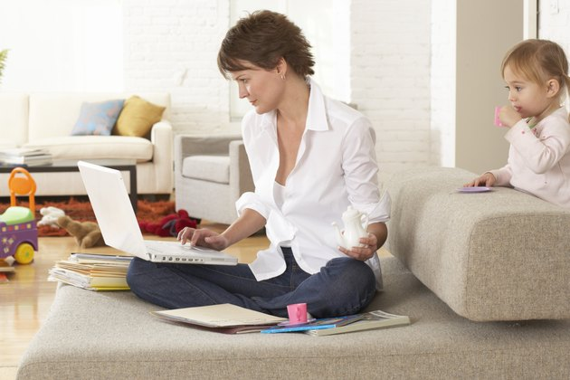 Woman using laptop on sofa by daughter (2-4) holding drink