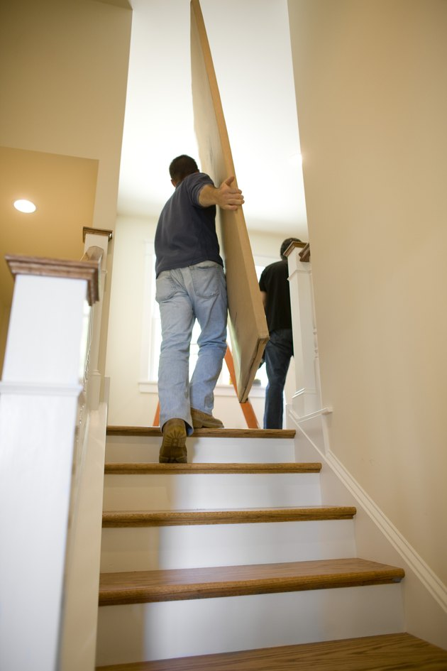 Contractors carrying boxes upstairs in house