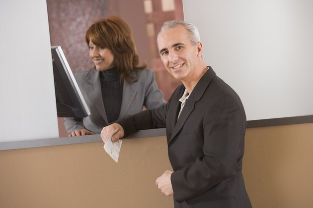 Man waiting at counter while receptionist checks monitor