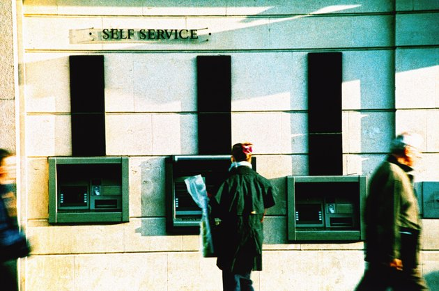 a person standing at an automatic transaction machine