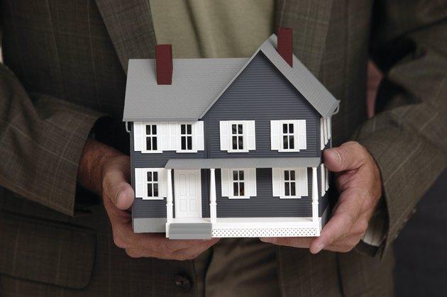 Man holding model house