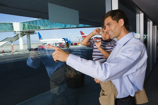 Man pointing out airport window for son