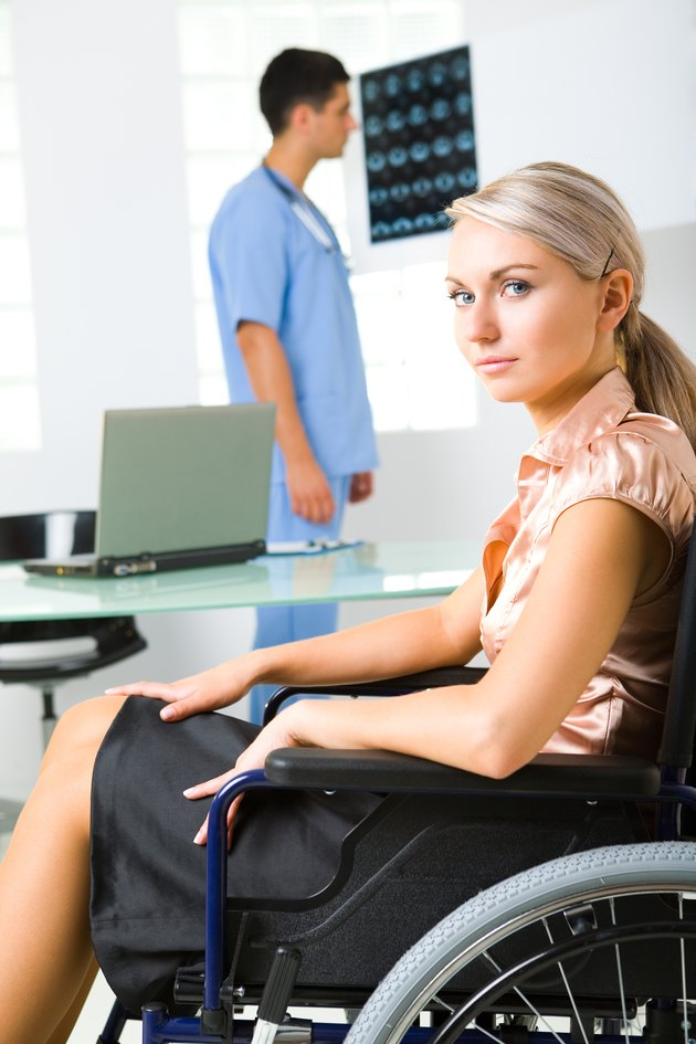 Woman in wheelchair with doctor analyzing imaging