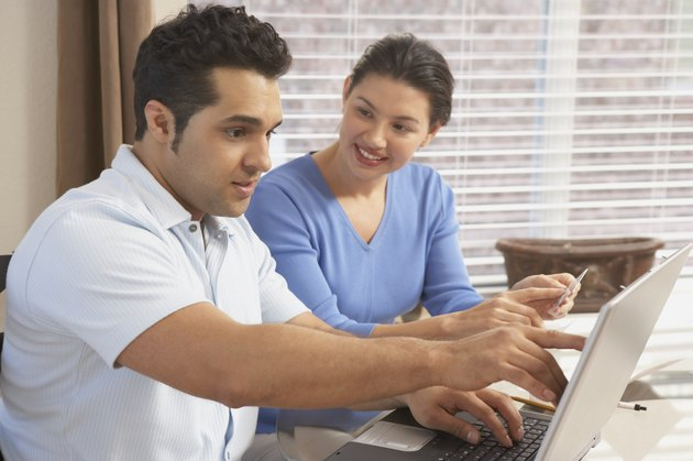 Side profile of a young couple in front of a laptop