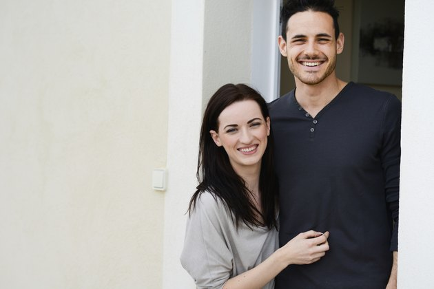 happy young couple welcome in new house at door entrance