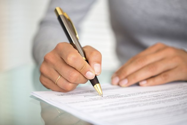 Woman at office desk signing a contract