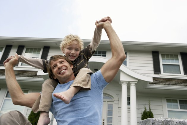 Boy (5-7 years) balancing on father's shoulders outside house, smiling
