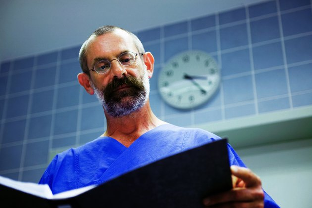 """Male surgeon in theatre, looking over notes, low angle view"""