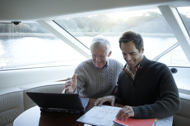 Senior and mature man sitting on yacht using laptop, smiling
