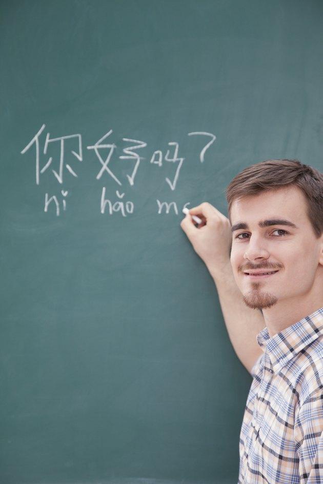 Portrait of smiling male teacher in front of chalkboard writing