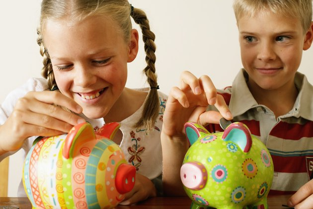 Twin brother and sister (10-12) dropping coins into piggy banks, girl laughing, close-up