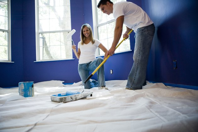 Young woman holding paint roller while young man preparing color