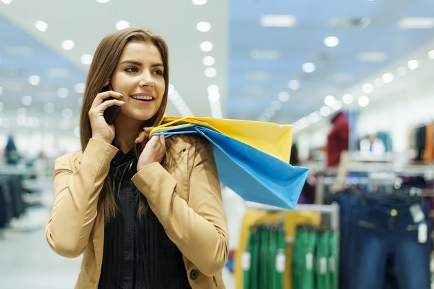 Young woman holding shopping bags and talking by phone