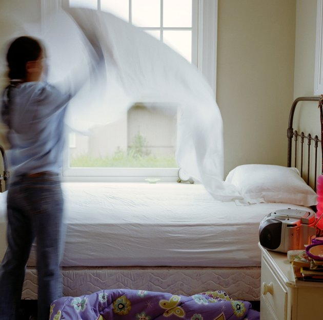 Girl (10-12) making bed, rear view (blurred motion)
