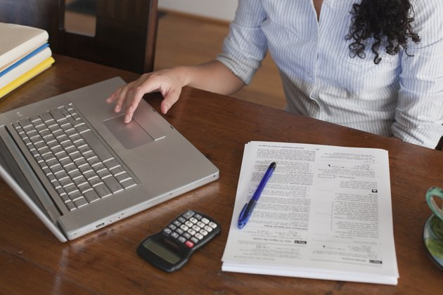 Woman Working on Laptop Computer, Calculator and Tax Documents at Dining Room Table, Detail