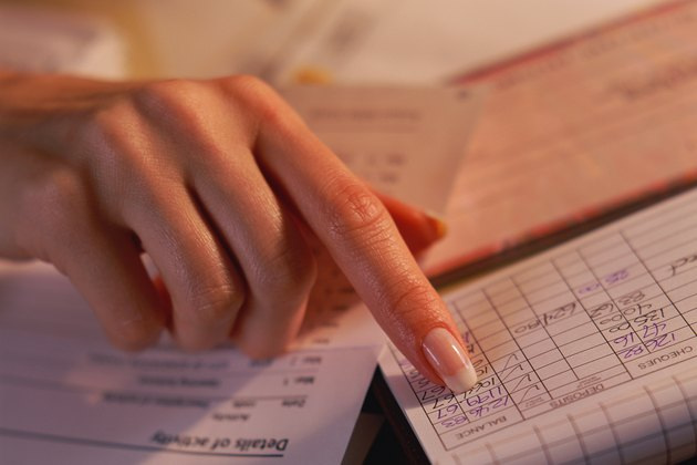 Finger pointing to balance in checkbook