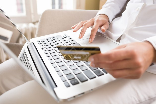 Woman holding a credit card and using computer, online shopping