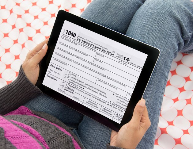 Person filing income tax returns online using tablet computer