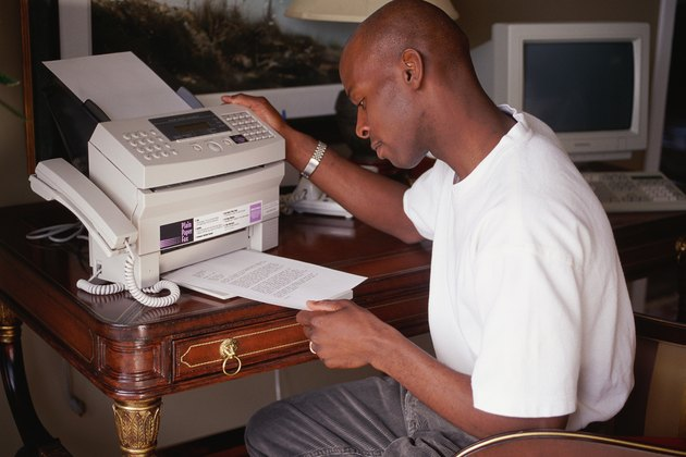 Man removing paper from fax machine