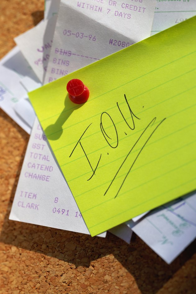 IOU and receipts pinned to cork board
