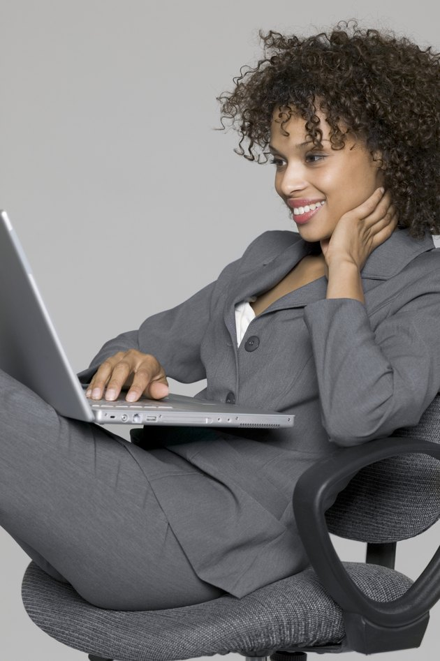 business portrait of a young adult female in a grey suit as she uses her laptop computer