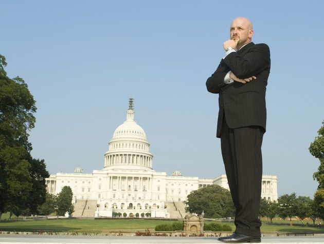 """Thoughtful Caucasian Man, Suit, Standing U.S. Capitol Building,"""