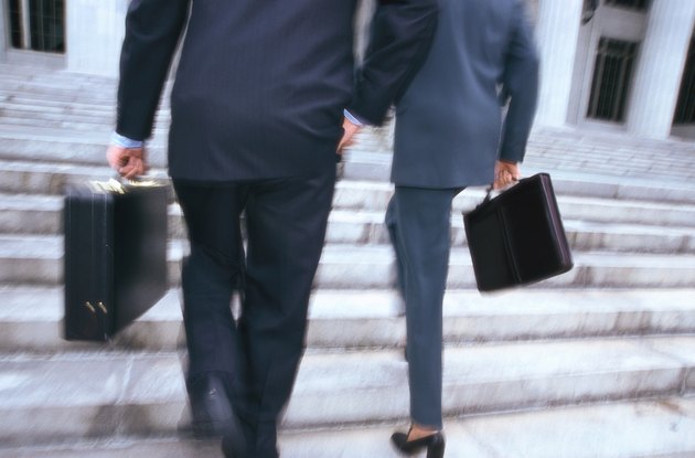 business executives with briefcases climbing stairs