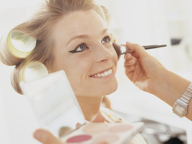 Make up Artist Applying Blusher to a Smiling Female Model
