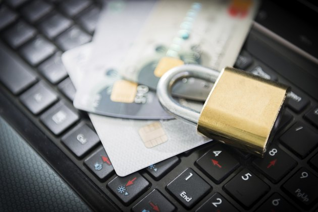 Padlock and credit cards on top of laptop