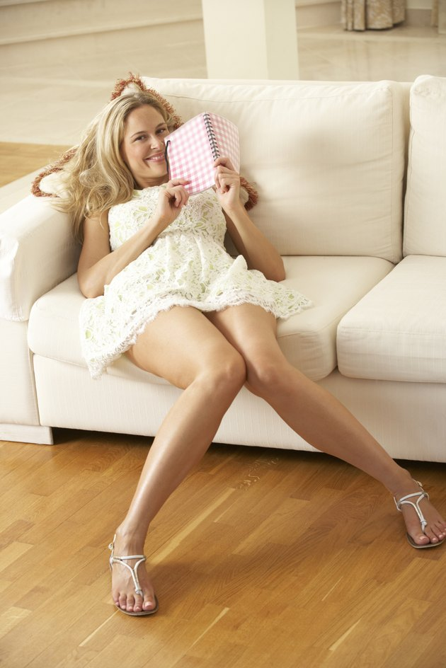 Woman Sitting On Sofa Reading Diary