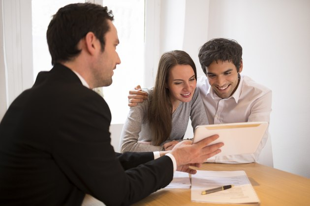 Young Couple meeting real-estate agent to buy property, presentation tablet
