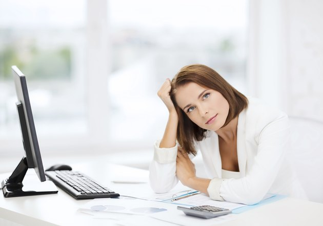 woman with computer, papers and calculator