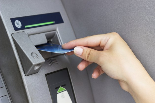Woman's hand puts credit card into ATM