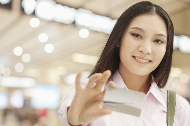 Smiling young woman showing her business card