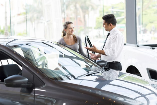 vehicle dealer showing young woman new car