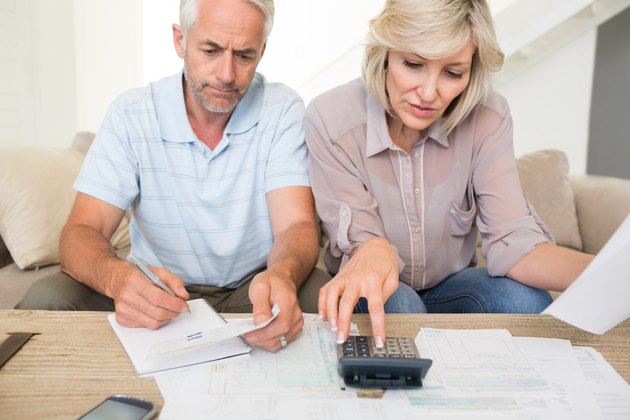 Concentrated mature couple with bills and calculator at home