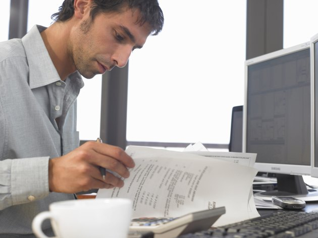 Businessman using PCs and looking at documents, close up, side view