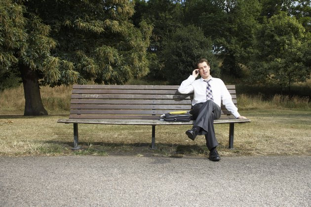 Businessman sitting on park bench, using mobile phone