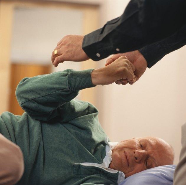 Senior man lying down having physiotherapy, focus on arm