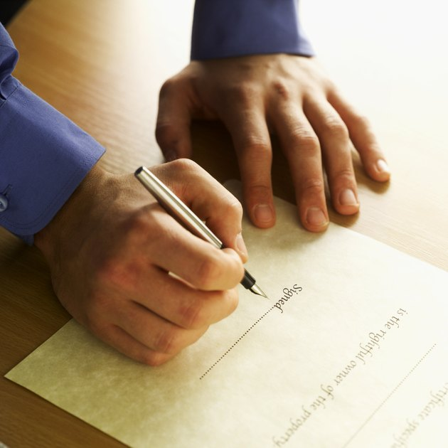 Close-up of man's hands signing house deeds with pen