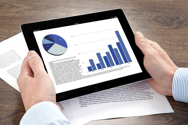 businessman holding a tablet with graphics on screen