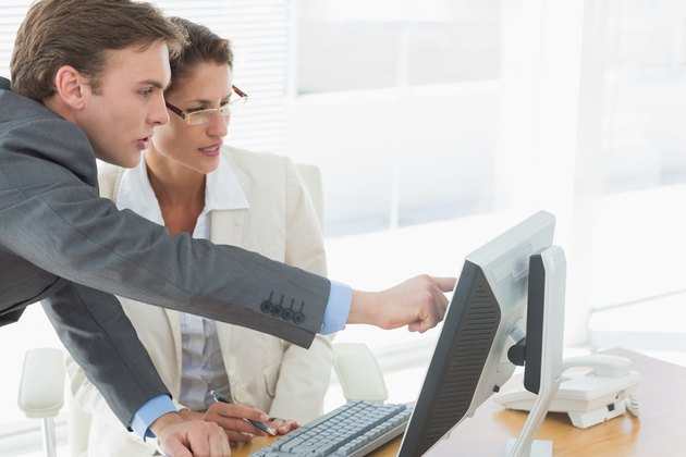 Business couple using computer at office desk