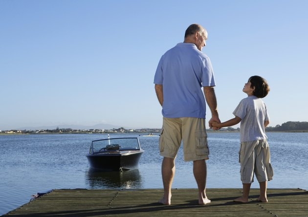 Father and son (6-8) holding hands on jetty, rear view