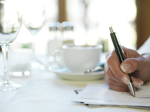 Woman in restaurant holding pen to paper, close-up of hand