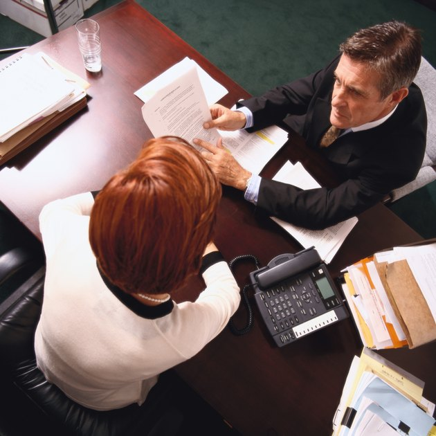 high angle view of a businessman explaining a document to a woman associate