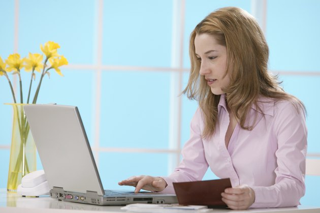 Woman using laptop with checkbook
