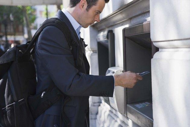 Businessman getting money from ATM machine