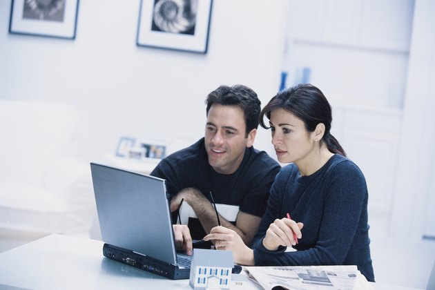 Couple with model house and laptop